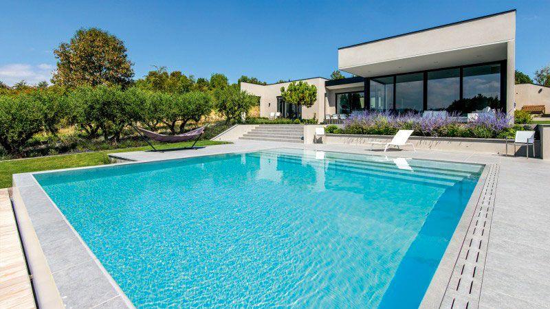 Pépite dans la colline piscine avec revetement gris clair Piscine miroir minéral Gris clair