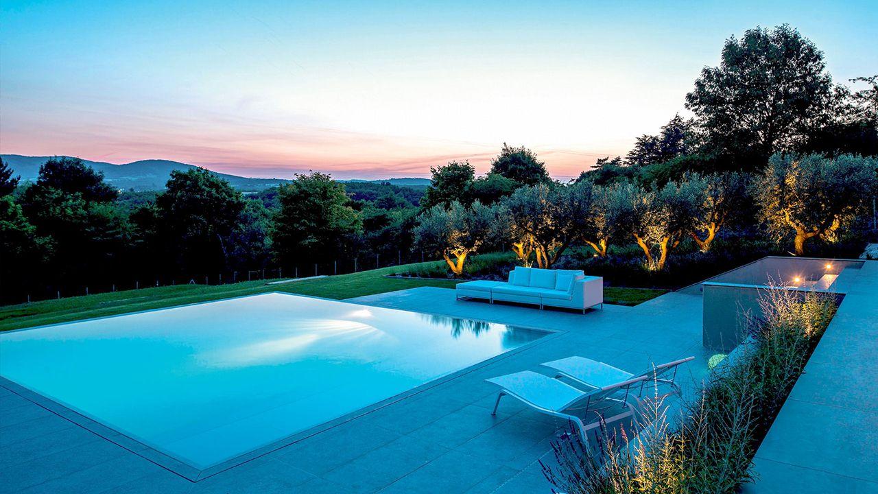 Pépite dans la colline piscine avec terrasse en gres Piscine miroir minéral Gris clair