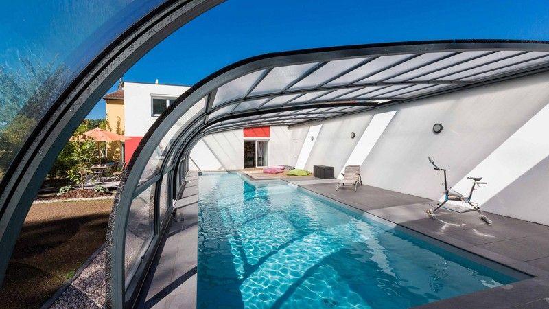 Hors d'atteinte du temps piscine couverte avec une veranda Gris clair