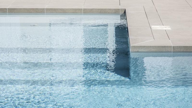 Terrasse à fleur d'eau pierre ceramique plage piscine Ligne d'eau minérale Gris clair