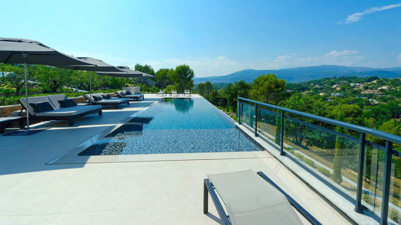Un monde infini piscine beton a debordement mosaique montagnes Piscine à débordement