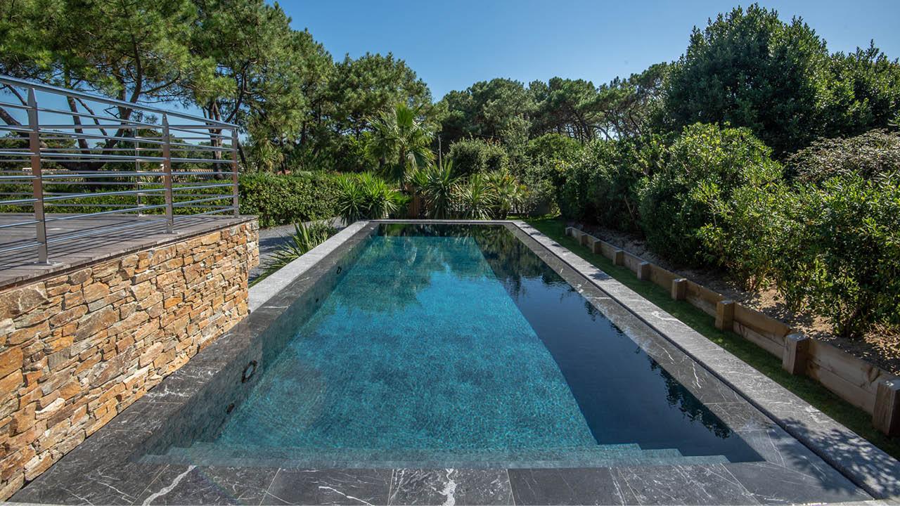 Eclat entre ciel et pierre piscine miroir hors sol avec vue sur la verdure Piscine miroir minéral 3D Gris ardoise