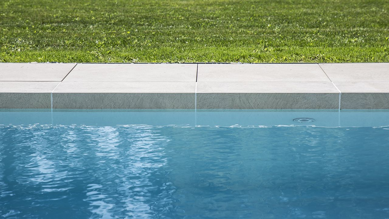 Terrasse à fleur d'eau bandeau ceramique piscine Ligne d'eau minérale Gris clair