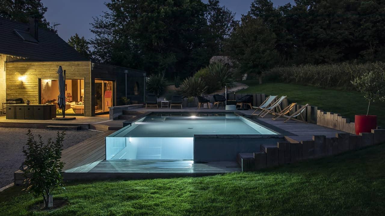 Pointe d'eau renversante Piscine debordement verre nuit terrasse esprit piscine 2020 52 Piscine à débordement Piscine à paroi vitrée Gris anthracite